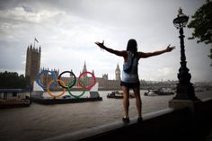 A tourist gestures in a rain shower as he looks at giant Olympic rings in the River Thames opposite Parliament on August 5, 2012 in London, England. (Photo by Peter Macdiarmid/Getty Images)