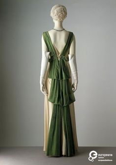 Evening dress of satin trimmed with velvet ribbons and diamantés, designed by Paul Poiret for Liberty & Co. Ltd., London, 1933. Evening dress of pearl satin trimmed with jade green velvet ribbons.... | Poiret, Paul (Designer)