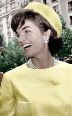 Jackie Kennedy in yellow suit, pillbox hat and pearls.