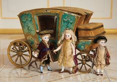 19th Century all-bisque mignonettes in court costumes, by a toy French coach, circa 1880s.