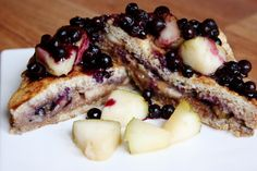 French toast stuffed with chocolate, peanut butter, pear slices and blueberries, topped with more pear and warm blueberries.