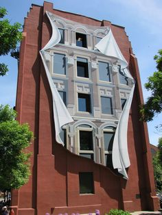 The wider side of the Gooderham Building (1892) in Toronto is marked by an artful painting made in the style of trompe l'oeil, meaning 'to deceive the eye.' The Flatiron Mural (1998) by Canadian artist Derek Besant, mirrors the building directly across from it. Derek gave the illusion of a fluttering drape and many open windows, only a few of which are actually there.