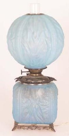 A Blue grass Unattributed Gone with the Wind Electrified table lamp formed of light blue glass. The pattern is remininscent of Tiffany's linefold glass. The base is square and has four feet. America, circa 1860-1890