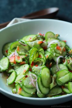An easy to make Asian Cucumber Salad that's full of crunchy cucumber, rice wine vinegar, and a few secret ingredients! Can be served as a refreshing summer salad or the condiment to a sandwich! veganize by using agave nectar in place of honey