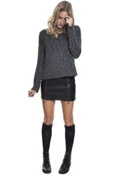 Blusa de tricô em fio flame com aplicação de tachinhas grafite fosco, saia preta de couro ecológico com zíperes na frente, bota tipo coturno e meia ¾ para agregar um estilo college.