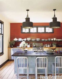 The designer chose Benjamin Moore's Merlot Red for one wall of this kitchen.  It sets off white dishware salvaged from a grand seaside hotel in France that was torn down.