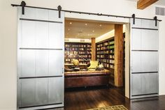 Entryway to library with silver sliding doors, wood floors, brown leather couch, and an assortment of books