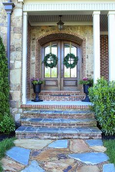 Double arched front doors, stone path, urn planters