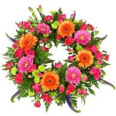 """A colourful seasonal wreath in shades of pink, orange, lime green and purple. Pretty and feminine, this loose wreath arrangement includes miniature gerberas, chrysanthemums and spray carnations, along with other seasonal blooms and foliage. Approximate sizes 10"""", 14"""" and 18"""" across."""