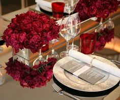 Gorgeous red peonies are arranged alongside votive candles and red rose petals in a silver metallic trough.