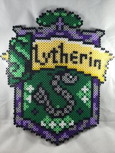Slytherin House Shield (Medium) * * perlercuteness.com * * #harrypotter #hp #slytherin #green #black #purple #perler #artkal #hama #fusebeads #yihatabeads #giftforgeek #giftfordork #giftfornerd #etsyseller #handmade #retro #pixelart #8bit Perler Bead Templates, Diy Perler Beads, Perler Bead Art, Melty Bead Patterns, Hama Beads Patterns, Beading Patterns, Pixel Art, Harry Potter Perler Beads, Hogwarts
