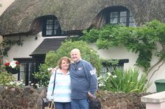 Kim and John outside a thatched cottage