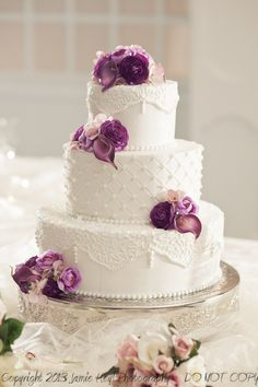 Simple white wedding cake with fresh purple flowers  Jamie Heyl photography