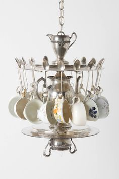 tea time chandelier- Eighteen vintage teacups dangle from an arrangement of vintage silver serving trays, utensils and the teapot itself, as seven lights illuminate the scene.