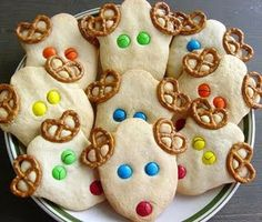 """Easy Reindeer Cookies  1 roll of pre-made sugar cookie dough  small pretzel rings  M & Ms  1 bell shaped cookie cutter  flour  baking sheet  Preheat oven to 350 F.  Mix  cookie dough and about 1/4 cup of flour to make the dough stiffer. Lightly flour the table. Roll dough out to 1/4"""".  Cut out 12 bell cookies.  Decorate as in picture."""