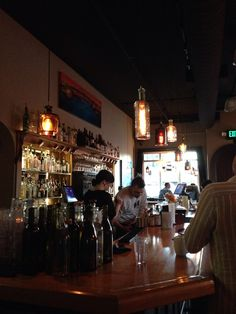 """Friends. Bar. Life is good. """"Each friend represents a world in us, a world possibly not born until they arrive, and it is only by this meeting that a new world is born."""" Anaïs Nin.   Attractive Lighting fixtures designed and crafted by Brendon Piskula, hanging in Alberta Street Pub, Portland, OR. Cheers!"""