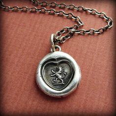 This pendants pictures a heart with a rampant lion in the center. In heraldry the Lion is a symbol for loyalty and devotion. A Lion centered in the heart is symbolic of love, trust and faith.