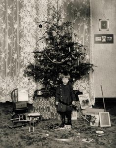 Small boy standing in front of a Christmas tree with his toys. (1900) ©Missouri History Museum