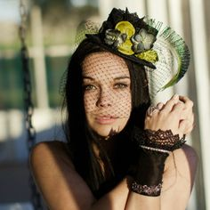 A beautiful black mini top hat with clusters of lime silk velvet rosettes and vintage grey petite flowers.  Backed with black French lace and a large peacock plume.  This hat is available with or without veiling.