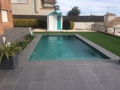 Esta piscina combina el gresite verde con un porcelánico exterior de color gris
