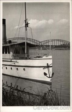Sailing Vessel on the Water with Bridge in the Background