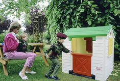 In the garden of her home in Highgrove, Princess Diana watches her sons play with a playhouse in 1986.