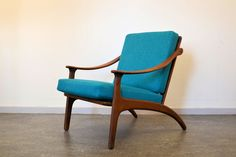 Danish teak lounge chair designed by Arne Hovmand Olsen for P. Mikkelsen during the 1950s. It has a shaped frame, new foam cushions with zippers and a new blue upholstery.
