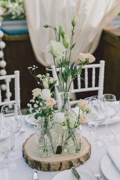 DIY idea: simple different height florals in different sized vases on a round of wood as table centrepieces