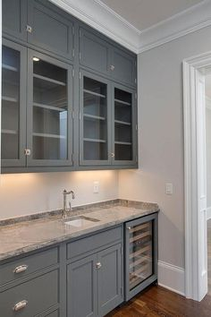 Grey butler pantry features glass front upper cabinets and gray lower cabinets fitted with a glass front wine cooler topped with grey granite. Grey Kitchen Cabinets, Upper Cabinets, Kitchen Redo, Kitchen Remodel, Pantry Cabinets, Grey Cupboards, Cheap Kitchen, White Cabinets, Grey Granite Countertops