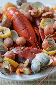 Clam Bake for Your Summer Kitchen _ It uses the cooking method of the low country boil, but the traditional ingredients of a New England Clam Bake. I included littleneck clams, chorizo sausages, shrimp, small red potatoes, corn on the cob & a lobster to top it all off. The butter, onions & herbs at the bottom of the pot blend with the juices of the food steaming above creating the most perfect dipping sauce!