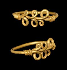 VIKING GOLD LOOPED BEZEL RING. 9th-11th century C.E. A round-section gold hoop with tapering ends forming a running scroll and coiled about the shank.