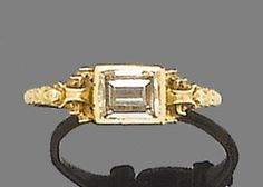 A 17th century gold and diamond ring, the central table-cut diamond in an elaborate scroll mount with engraved decoration