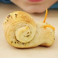 (For the kids) Breadstick Snails  Heat to 375. Unroll dough and separate into strips. Spread strips with pesto or seasoned butter and roll up into a coil, leaving a curved end, so it looks like the head of the snail. Secure with a toothpick. Place upright on a baking sheet.  Bake for 10 minutes. Poke holes for antennae; insert two carrot slivers.