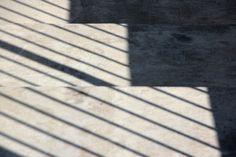 Fotografie van vlakken: een donkergrijs vlak en een lichtgrijs vlak. het lichtgrijze vlak wordt doorkruist door donkergrijze evenwijdige lijnen. Deze vlakken zijn ontstaan door schaduw.