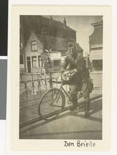 Anonymous | Duitse soldaat met fiets op een brug, Anonymous, 1940 - 1943 | Op een brug in Brielle poseert een Duitse soldaat met een fiets. Hij draagt een legerpet en een bril. Achter hem huizen en een ANWB bord dat wijst naar o.a. Oostvoorne, Hellevoetsluis, Maassluis en Den Haag. Half zichtbaar achter de soldaat is een bord in het Duits te zien. Achterop staat: Mein Fahrrad ist gründlich überholt, neue kette etz. (Weer zelfde persoon als op NG-2007-5-35 t/m 38).