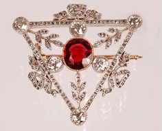A Russian 56 standard gold, diamond, and spinel brooch attributed to Faberge (maker's mark partially overstruck by the assay mark), of triangular form; each side adorned with a diamond set bow; the garnet supported by three diamond set, leafy branches and three mine cut diamonds. bearing a later engraved inventory number 2157.