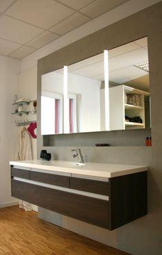 Badmöbel mit in Wand eingebautem Spiegelschrank, Wand in Betonoptik.