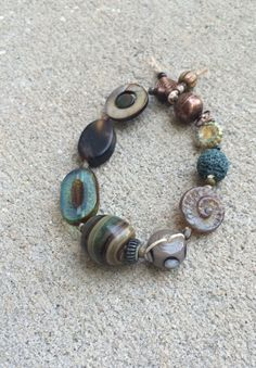 Another brown and blue bracelet with glass, czech table cut, shell, stone, copper, and lava beads knotted on natural Irish waxed linen with magnetic copper clasp. Handmade jewelry. By caislinS