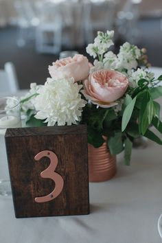 Wedding table decor. Beige linens, floating candles, wood and copper table numbers, floral centerpieces in copper cans. Juliet garden rose, china mum. bay laurel, white stalk.