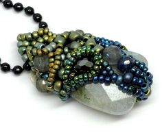 This Fairy Chrysalis pendant contains a green flash labradorite for its core. The outside is encrusted with a variety of gemstone beads including blue sapphire, labradorite, green tourmaline, and black cubic zirconia. The seed beads are a rich mixture of cool metallic colors including blue, green, matte silver, and a touch of matte gold.
