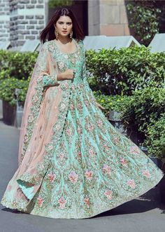 Green anarkali suit embellished in floral embroideryGreen anarkali suit featuring in silk. Its embellished in zari and resham embroidery along with mirror in floral motif. Matched with lycra churidar and dupatta in pink embroidered net. Slight variation in color is possible