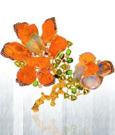 Orange fire opal flower brooch featuring 78.6 carats of rough orange fire opal and 27.94 carats of mixed opal cuts set in 18K yellow gold. By Lugano Diamonds.  #LuganoDiamonds #FireOpalBrooch #VonGiesbrechtJewels