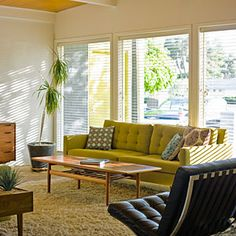 The living room of this midcentury ranch home is designed to mesh with the retro style of the architecture, but with fresh touches that keep the look current. The Danish-modern coffee table was purchased on eBay and the side table/planter at an antiques mall for $40. New items include a Crate and Barrel sofa and a flock of Etsy pillows.