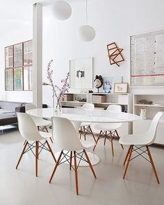 Maybe no rug? Clean modern dining room with Eero Saarinen table and Charles and Ray Eames molded chairs in the apartment in the center of old Madrid, designed by