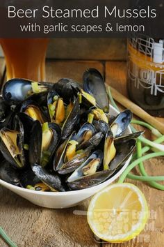 An easy appetizer or light meal these beer steamed mussels tossed with garlic scapes and fresh lemon are quick to make and bursting with flavor via earthfoodandfire Mussels Recipe Beer, Mussels Seafood, Steamed Mussels, Grilled Mussels, Shellfish Recipes, Seafood Recipes, Seafood Dishes, Fish And Seafood, Seafood