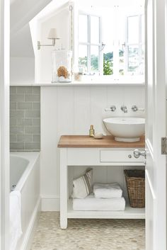 White cottage bathroom features French windows over a white washstand topped with butcher block lined with a round bowl sink under a wall-mount vintage faucet lining a vertical shiplap wall placed atop a tan pebble floor. Cottage Bathroom, Bathroom Styling, Bathrooms Remodel, Country Bathroom, Bathroom Design, Beach House Bathroom, Small Remodel, Small Bathroom Remodel, Bathroom Design Decor