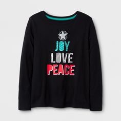 """She can show off her holiday spirit with the Long-Sleeve Holiday T-Shirt from Cat & Jack™. This long-sleeve graphic T-shirt is decorated with the words """"Joy, Love, Peace"""" in green, white and red, stacked on top of each other to create the shape of a Christmas tree, complete with a star on top. She'll love to pair this with Christmas-themed leggings or a sparkly tulle skirt for a festive holiday outfit."""