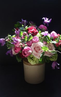 Old earthen wear pots stuffed with shades of purple  pink. Clemitis, Peonies, Viburnam  Sweet Avalanche roses.