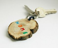 """keychain made from a piece of wood, with the words """"home"""" painted on it in blue, orange, red and green, with a key attached, on a white background"""
