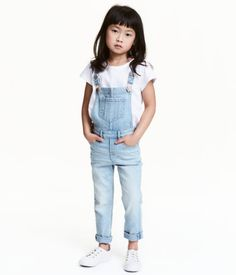 Light denim blue. Bib overalls in washed superstretch denim. Adjustable suspenders with metal fasteners, chest pocket, and front and back pockets. Mock fly